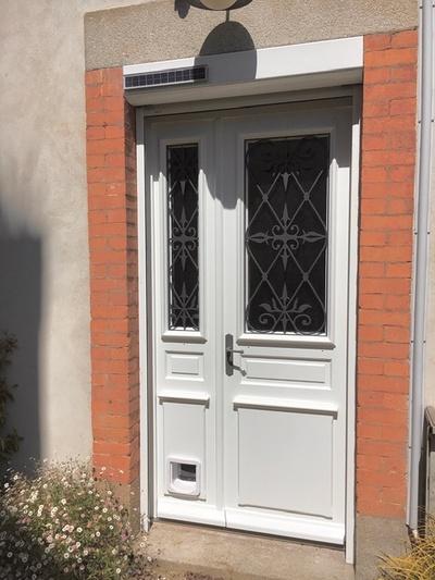 Installation d''une porte d''entrée sur-mesure en bois avec grille en fer forgé