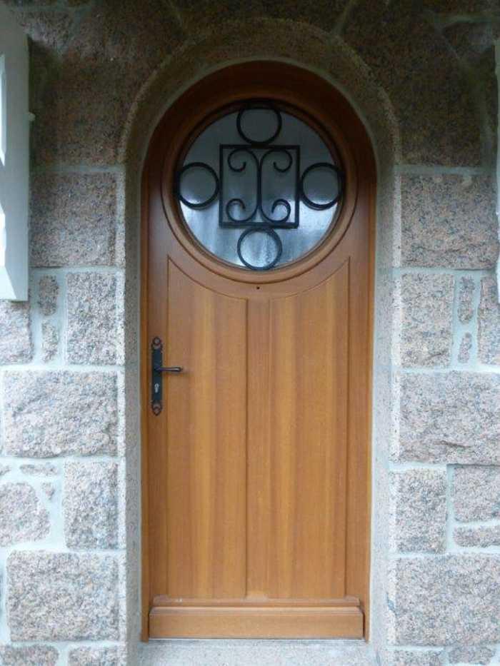 Réalisation d'' une porte d''entrée cintrée vitre circulaire sur-mesure en bois 0